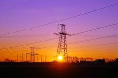 Linee elettriche ad alta tensione di distribuzione pilone al tramonto Immagine Stock Libera da Diritti