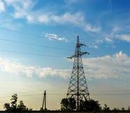 Linee elettriche ad alta tensione di sostegno contro il cielo blu Fotografia Stock Libera da Diritti