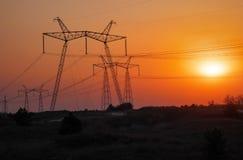 Linee elettriche ad alta tensione durante l'alba Fotografia Stock