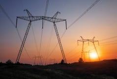 Linee elettriche ad alta tensione durante l'alba Immagine Stock