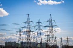 Linee elettriche ad alta tensione nei precedenti della città Stazione elettrica di distribuzione Immagini Stock Libere da Diritti