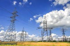 Linee elettriche ad alta tensione nel campo con grano dorato ed il bello cielo blu con le nuvole bianche Fotografia Stock