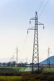 Linee elettriche ad alta tensione nella valle che allunga nel dista Immagini Stock