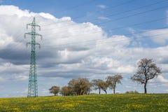 Linee elettriche ad alta tensione sopra il prato della molla Fotografia Stock