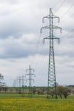 Linee elettriche ad alta tensione sopra il prato della molla Pali di elettricità Fotografie Stock Libere da Diritti