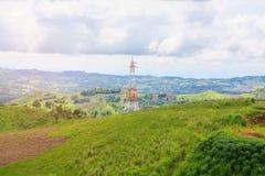Linee elettriche ad alta tensione torre sulla montagna verde Fotografia Stock