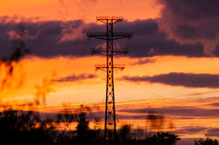 Linee elettriche del cuscinetto su un tramonto Fotografie Stock Libere da Diritti