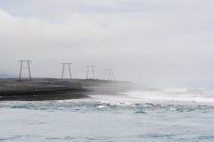 Linee elettriche e piloni sulla riva nera del mare del Nord, Icela Fotografie Stock Libere da Diritti