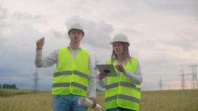 Linee elettriche, un uomo ed ingegneri di una donna con una compressa in loro mani che discutono il progresso della costruzione stock footage