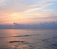 Linee gialle dorate in cielo variopinto di mattina con l'orizzonte luminoso del sol levante sopra l'oceano con la riflessione in  immagini stock libere da diritti