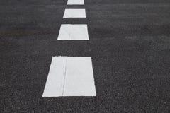 Linee marcatura bianche di traffico sulla strada asfaltata Fotografia Stock Libera da Diritti