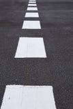 Linee marcatura bianche di traffico sulla strada asfaltata Fotografia Stock