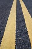 Linee marcatura gialle di traffico sulla strada asfaltata Immagini Stock Libere da Diritti