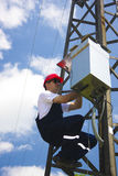 Lineman do eletricista da potência no trabalho no pólo Foto de Stock