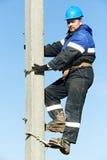 Lineman do eletricista do poder no trabalho no polo Fotografia de Stock