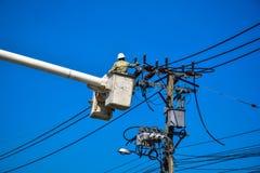 Lineman do eletricista que repara o trabalho no polo de poder bonde do cargo Foto de Stock