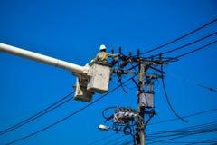 Lineman do eletricista que repara o trabalho no polo de poder bonde do cargo Foto de Stock Royalty Free