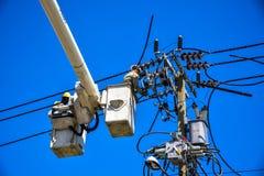 Lineman do eletricista que repara o trabalho no polo de poder bonde do cargo Fotos de Stock