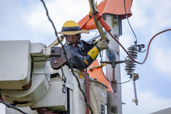 Lineman Repairs Electricity Distribution Lines From An Elevated Stock Photo