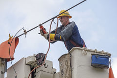 Lineman Repairs Electricity Distribution Lines From An Elevated Stock Photography