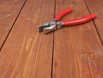 Lineman's combination pliers hand tool on wooden surface Stock Images
