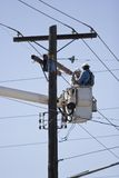 Linemen. Vertical Photo of Linemen Utility Workers working on phone lines from bucket truck with blue sky Stock Images
