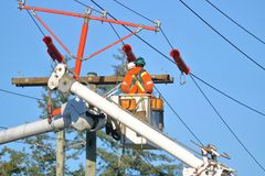 Linemen Connecting New Electrical Power Line. Close on linemen in a bucket as they connect an electric line for new power poles that have been newly installed Royalty Free Stock Images