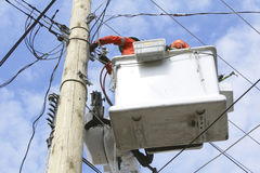 Linemen at Work. Linemen hook-up new powerlines for a hydro pole Stock Photos