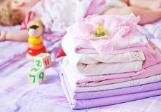 Linen. Baby clothes on the bed, color baby linen Royalty Free Stock Photography