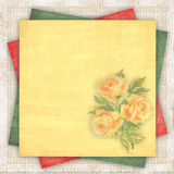 Linen background with a multi-coloured paper. Linen fabric background with a multi-coloured paper and with the embroidered yellow roses Royalty Free Stock Image