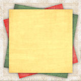 Linen background with a multi-coloured paper. Linen fabric background with a multi-coloured paper of three colours Stock Images