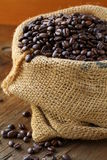 Linen bag with coffee beans. On wooden table Royalty Free Stock Photography