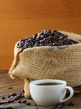 Linen bag of coffee beans and a cup of espresso. On a wooden table Stock Image