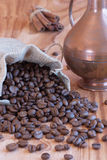Linen bag with coffee beans, a spoon and oriental. Teapot and cinnamon Stock Photography