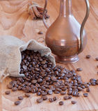 Linen bag with coffee beans, a spoon and oriental. Teapot and cinnamon Stock Photos