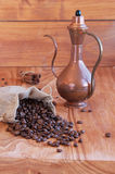 Linen bag with coffee beans, a spoon and oriental. Teapot and cinnamon Royalty Free Stock Photography