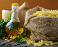 Linen bag of pasta (penne) and a bottle Royalty Free Stock Images