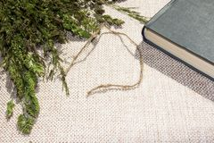 On linen cloth. On linen cloth, lies a bouquet of field green grasses, a jute thread for bookmarks and a book Royalty Free Stock Photo