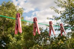 Linen clothespins on ropes against the blue sky royalty free stock photos