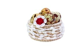 Linen crochet lace basket with Easter quial eggs and crochet colorful flower isolated on white background. The photo of Easter, sp stock image