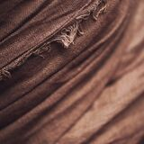 Linen crumpled crease brown background. Close up