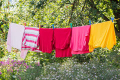 Linen is dried on rope in the garden. Linen is dried on a rope in the garden Stock Photo
