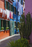 Linen dries above the small street of colorful Burano Stock Images