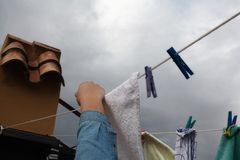Linen dries in the rain. She takes drying linen before the rain Stock Photos