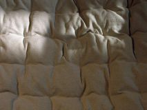 Linen fabric 2. Shadowed beige linen bed cover Royalty Free Stock Photography