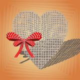 Linen heart with a red bow. On an orange background Royalty Free Stock Image