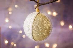 Linen and lace Christmas tree ball with ornament hanging on a branch. Golden garland glittering light in background. Greeting card Stock Photography