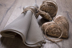 Linen napkin tied by cord with crude wooden heart Stock Photos