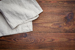 Linen napkin on wooden table. Linen napkin on brown wooden table Stock Image
