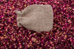 Linen sack on Background of dried  rose petals. Linen sack placed  on Background of dried  rose petals royalty free stock photography